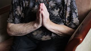 Very old woman praying at home