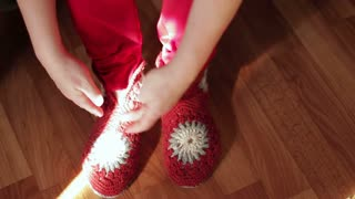 Woman putting on a red hand-made shoes.Close up