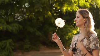 Young beautiful girl blowing out a huge dandelion
