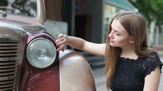 Young beautiful woman next to a vintage car
