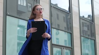 Young Business lady is waiting for a partner near an office building