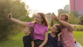 Young family doing selfie in the park. They have fun and spend time together. The concept of a friendly and cheerful family