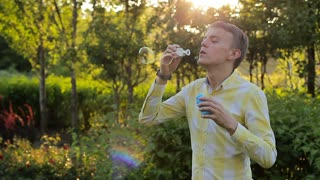 Young man blowing soap bubbles at sunset in the garden