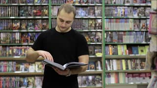 Young Man buying a book in a bookstore