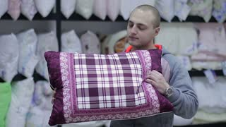 Young man buys a pillow in the store. He stares and twirl it in the hands of
