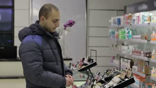 Young man chooses cosmetics. he wants to make the girl a gift.