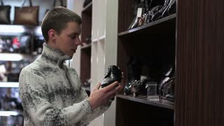 Young man chooses shoes at shoe store