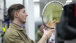 Young Man chooses sporting goods in the store. Tennis racket. Close up