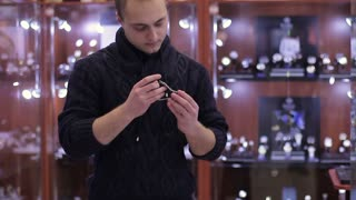 Young Man chooses wrist watch in the watch store