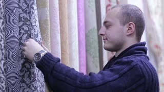 Young Man choosing curtains in shop.