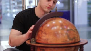 Young man examines a globe in a travel agency.