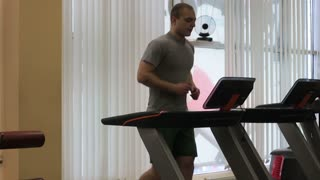 Young man in sportswear running on treadmill at gym