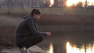 Young man meditating at sunset