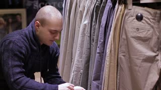 Young Man Shopping for Jeans in Store. Close up
