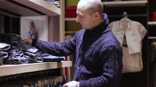 Young man Shopping for Jeans in Store.