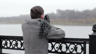 Young man standing on the bridge by the river and looking at the city on a cloudy cold day