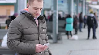 Young man waiting for a bus at the bus stop and using a smartphone