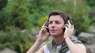 Young man with headphones listening music outdoor. He looks up and enjoys the rain and enjoys the music