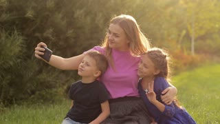 Young mother with children making selfie on smartphone. They have fun taking photos for a family album