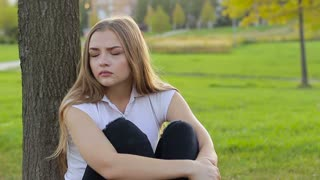 Young sad girl sitting under a tree