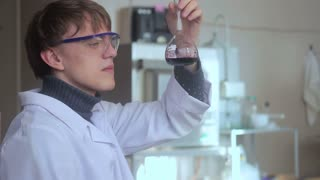 Young scientist in laboratory examining liquid in glass beaker.