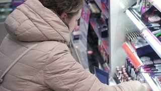 Young woman chooses lipstick in cosmetics shop