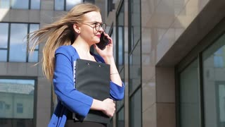 Young woman talking on the phone in the background of the business center