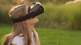 Young woman uses head-mounted display. Playing game using VR-helmet for smart phones