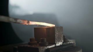 Blacksmith forging a hot iron with a hammer.