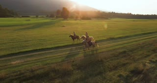 Girls Riding Horses In A Sunset
