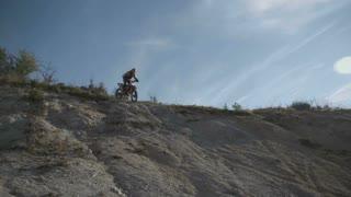Motocross rider driving downhill.