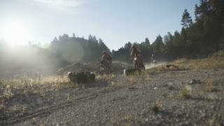 Motocross riders driving on motocross trail.