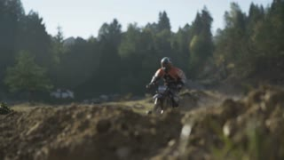 Rider driving and jumping on motocross trail.