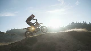 Riders driving and jumping on motocross trail.