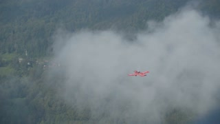 Small red airplane flaying above forest troughs the clouds.