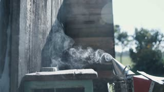 Smoke from a bee smoker, in the background is a barn