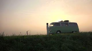 Vintage camper van is driving at the sun set.