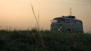 Vintage van is driving at sunset.