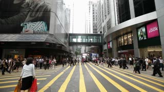 A busy pedestrian intersection in Hong Kong overflows with people