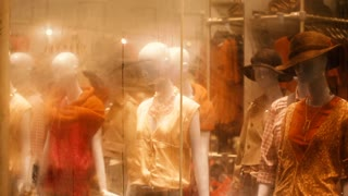 A collection of fashionable Mannequins sit behind a wet window in Singapore