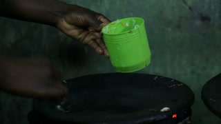 A cook at a Uganda restaurant pours food from a cup to a hot plate