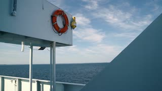 A life preserver hangs over the deck of a ferry moving along Long Island