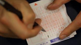 A man fills out a horse-race betting card in Hong Kong