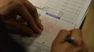 A Man's Hands fill out an Asian betting form for Horse Racing