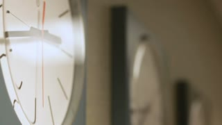 A series of minimalistic clocks tick away with focus on the foreground clock