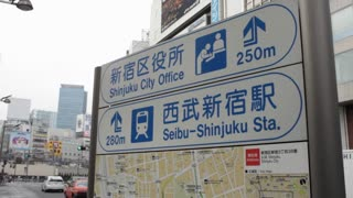 A sign and map point to Seibu-Shinjuku Station, with traffic in the background.