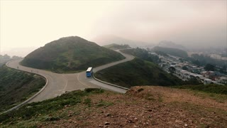 A tourist Bus navigates San Francisco's Twin Peaks on a foggy morning
