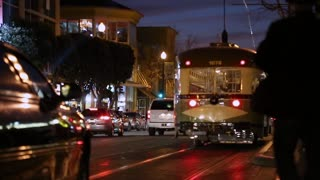 A vintage San Francisco Streetcar / Trolley moves through traffic at Night