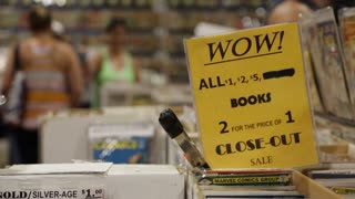 A yellow sign advertises Sales at a Comic Book Stand at Comic-Con