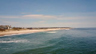Aerial shot above the ocean closes in on boardwalk on East Hampton Main Beach